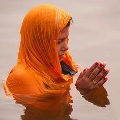 woman praying in water, India