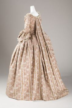 Side view, robe à la francaise (sack-back gown), France, 1760-1780. Striped salmon-coloured brocaded silk. A white leaf pattern is woven into the fabric and as well as floral sprays in various colours.