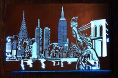 'New York City Skyline' by day & night. Ask us to incorporate LED strip lighting so you can enjoy your metal wall art by night!