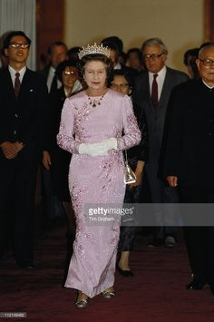 Queen Elizabeth II attending a banquet, held in the Hall Of The People, Beijing, while on an official state visit to China, 13 October 1986. The dress worn by the Queen is decorated with tree peony blossom, the national flower of China, and was designed by Ian Thomas. Foreign Minister Geoffrey Howe is in the background. (Photo by Tim Graham/Getty Images