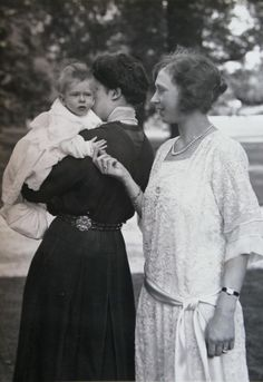 Princess Mary, Countess of Harewood with her first child George, who is being held by a nanny.