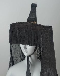 Woman's hat | France (Burgundy, Bourg-en-Bresse), 19th century | Materials: lace | Woman's hat (brelot). Flat brim; high, small conical crown. Covered with black lace; four deep black lace pendant bands. Brass chain around base of cone | Museum of Fine Arts, Boston