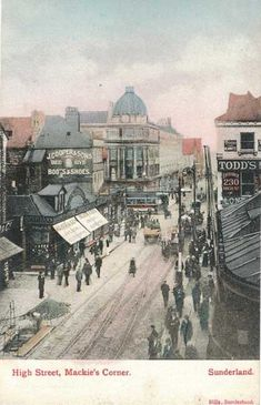 """MACKIE'S CORNER: An unused, undated postcard but obviously the early 1900s. Immediate right, the entrance to the north end of the Railway Station. Apparently Todds sold blankets, gloves and furs. Opposite Todds, Walkers Opticians and Jewellers. Adjacent to them, J.Coopers and Sons Boots and Shoes Shop. Their trademark was a beehive which can be seen on the corner of the third storey of the building level with and to the right of the word """"Sons"""""""