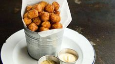 "Tater tots have come a long way from the grade-school cafeteria. Ore-Ida introduced the little potato treat to the world in the 1950s, a product created simply to use up extra potato peels and slivers. Today tater tots (or ""pom-poms"" as the Australians say) come with truffle or mole ..."