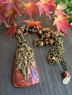 This Picture Jasper Necklace with Antique brass filagree is nature inspired with its fall earth tone colors. The semiprecious stones are beautiful on their own but really stunning when mixed with the antique brass bead caps, chain, and filagree. This piece is 28 to top of pendant gemstone, with 2 additional length for adjustment. The jasper gemstone is about 2 high and 1 1/4 at the widest point. This necklace has a very earthy feel and will never go out of style. All metal components are…