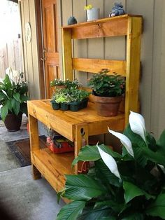 a bench made out of pallets to show off potted plants around the garden....