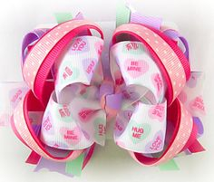 Girls Conversation Hearts Valentines Day hair bow made in a mix of lavender, pink, shocking pink, and candy hearts print ribbon. This bow