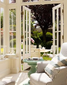 English Terrace | The back terrace of designer Colette van den Thillart's London home incorporates the best of the English country aesthetic. Mismatched stripes on the armchair mirror the slatted cafe chairs outside. The cerulean pedestal used as a side table evokes a garden bird bath, bringing the outside in.