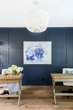 Home office with Benjamin Moore Hale Navy board and batten wall, navy blue and white abstract artwork, whitewashed bead chandelier, wood desks and Mannington white oak Maison Normandy Bistro hardwood floors.