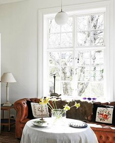 Has: High ceilings, large window, GREAT Chesterfield.  Needs: Ditch the table skirt and granny pillows.  Get a statement lamp, curtains, art.