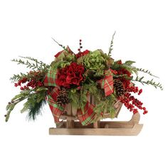 Featuring a sleigh-shaped planter, this faux hydrangea and berry arrangement offers seasonal charm for your home.  Product: Faux...