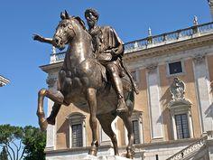 --Estatua de Marco Aurelio (copia)-- Marco Aurelio Antonino (121-180 d.C.), emperador romano (161-180 d.C.) e filósofo estoico, pai do emperador Cómodo. Esta estatua de bronce data do s.II d.C. Estaba no pedestal do centro da Piazza do Campidoglio, pero agora foi restaurada e está no Palazzo Nuovo. Na praza temos unha copia.