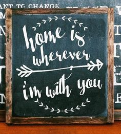 "This hand-painted wood sign celebrates who you call home, reading, ""Home is wherever I'm with you."" The lyrics are lettered by hand and surrounded with a leafy wreath and arrow illustration in your choice of paint color. The square signage is built and framed in solid wood and distressed to add a rustic touch to any part of your home."