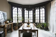 Eclectic Dining Room - Mullioned windows in a dining room with a tile floor