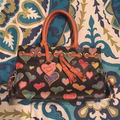 Dooney & Bourke Bag Mini Dooney & Bourke bag with multicolored hearts. Hearts look like they were drawn with crayon. Super cute for a little girl's first bag! Dooney & Bourke Bags Mini Bags