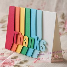 handmade Thank You card ... clever design with letters of THANKS cut on the edge of columns of colored paper in rainbow order ... probably used a cutting machine ... great card!!