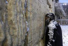 Un judío ultra-ortodoxo cubierto de nieve rezando en el Muro de las Lamentaciones