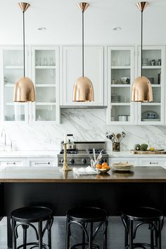 white & glass cabinets. Dark island. Copper lighting.  Contemporary Traditional Kitchen: A trio of hammered-copper pendant lamps above a custom wood island in a whitewashed kitchen.