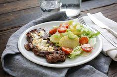 Recept voor aardappelsalade en karbonade voor 4 personen. Met zout, boter, peper, aardappelschijfjes, karbonade, bleekselderij, cherrytomaat, geitenkaas, zuiveldressing (mosterd-kruiden) en ijsbergsla