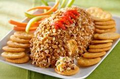 Cheesy Football recipe -What's more welcome at a game-day party than a cheese ball? A cheese ball that looks like it belongs in the game, of course. Three cheeses team up for some serious yum