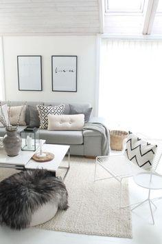 Sala de estar com tapete creme, sofá cinza claro, almofadas, manta decorativa, cadeira e mesa de centro branca. Dicas e Inspirações de Mantas para Sofá