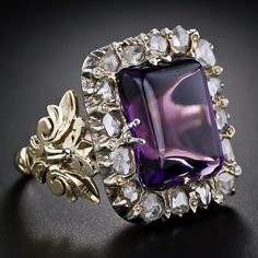 A succulent grape flavored amethyst - actually, this deep purple rectangular cabochon amethyst does indeed resemble a grape flavored hard candy - is set in a silver frame of glittering rose-cut diamonds and is borne by gracefully sculpted 14 karat gold shoulders and an open-work gallery.