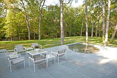 A unique water feature is set into the gray ground of this modern terrace, adding to the tranquility of the natural scene. Meanwhile, powder-coated white metal furniture is low and minimal, inviting conversation.