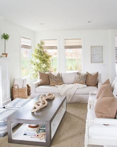 A fall living room decorated in brown tones with blue and white accents. Walls are Benjamin Moore Simply White. #livingroomdecor #livingroomdesign #falldecor