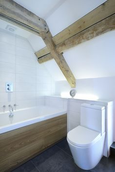 O2i Design's architects revived this characterful period farm outbuilding and overhauled this dilapidated period barn on the Somerset Levels. The result is a contemporary home with exposed wooden trusses and stonework in a light modern and interior. #bathroom #bath #beams #barnconversion © O2i Design Limited.