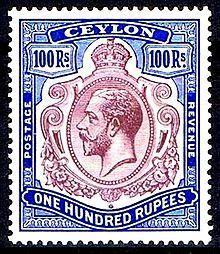 Un mint muy valorizado de 100 rupias key type stamp de Sri Lanka válida como franqueo o fiscal y vulnerable al lavado para remover una cancelación fiscal para valorizarla como mint
