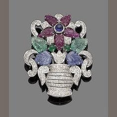gem-set giardinetto brooch  The brilliant-cut diamond urn, issuing stylised flowers with carved ruby, emerald and sapphire petals and leaves, highlighted by a cabochon sapphire bud