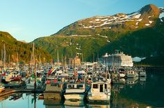 Photo of the boats docked in the marina and a cruiseship at the harbour of Whittier, Alaska on a clear, summer day.