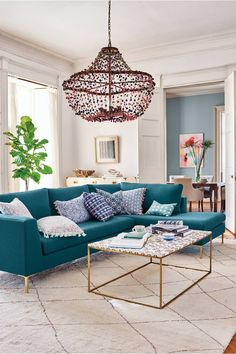 Living room with a blue sofa and a colorful Anthropologie chandelier