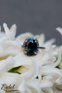 This ring features a 3.7ct oval sapphire. The color is a gorgeous, deep peacock green with blue flashes.  View our collection today!