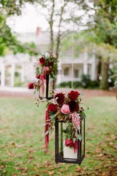 Burgundy and pink flowers decorating hanging lanterns. Marsala wedding flower ideas