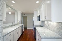 Kitchen: Monochromatic White Kitchen Furnitures With White Granite Countertop On The Wooden Floor Mixed With Ceiling Lamps And White Bricks Wall Tile: A Modern Granite Countertop Designing As Your Adorable Kitchen