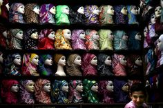 A Syrian youth waits for customers in a shop selling head scarves at the popular Hamidiyeh old market, in Damascus, Syria, Thursday, Aug 22, 2013.