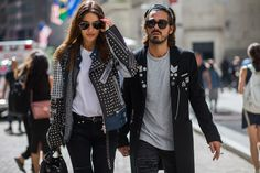 Patricia Manfield wears a studded leather jacket, white t-shirt, belted jeans, a bucket bag, and aviator sunglasses