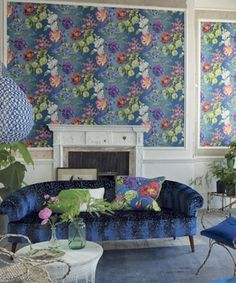 A gorgeous and rich floral wallpaper in fuchsia, violet and green on a gently shading ombre blue background.