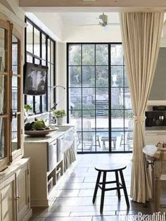 "Hang an interior curtain. In the kitchen of an Atlanta house, a linen curtain runs on a track spanning the room and can be pulled ""to conceal the mess of preparation,"" designer Beth Webb says. Steel-and-glass casements frame views of the pool and garden. KWC Gastro faucet"