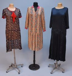THREE DAY DRESSES, 1920's. One long sleeve ecru crepe with blue and rust Deco print with cherries. One short sleeve cotton voile with navy, red and cream geometric print having ruffled cap sleeve and red trim. One navy crepe with 3/4 sleeve, navy floral embroidery and pleated skirt panels.