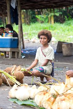Young girl selling coconuts at a roadside market, Papua New Guinea