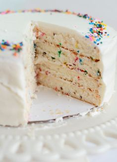 Funfetti Cake with Buttercream Frosting - the fun is all in the assembly, white buttercream frosting and sprinkles. #HelloColor #Yum