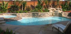 Custom swimming pool with ledger stone raised wall, natural stone spillway from spa to pool and a rock waterfall. Splash Pools and Construction can provide services for all your outdoor living needs.