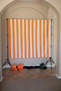A Halloween Photo Booth is a great way to give your guests a place to take pictures of their amazing costumes!  I like to keep it simple.  Here I used a shower curtain with painted orange stripes as a backdrop.  I added some plastic pumpkins and a black boa as props for a festive Halloween backdrop.