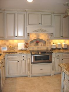 Kitchen remodel with custom built cabinets, granite countertops and tumbled  marble backsplash with niche behind