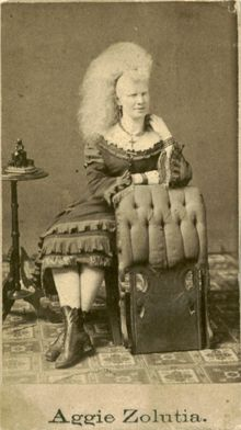 An albino Circassion beaauty who went by the name of Aggie Zolu. P. T. Barnum at his American Museum in 1864 exibited ladies with teased hairstyles and claimed they were Circassian ... but most times not. They often performed as sword swallowers or acrobats and almost always had exotic names...