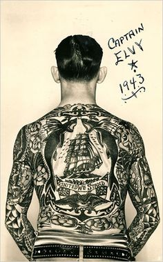 "A photo, circa 1940, of ""Captain Elvy"" and his tattoos. His back features a clipper ship, roses, flying fish, eagle, American flags and a banner reading ""United We Stand."""