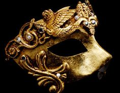 This mask is painted in aged effect antique gold and adorned with ornate designs. Faux diamond crystals bring a rich highlight to the mask. This Venetian mask is for men or women. With traditional black satin ties