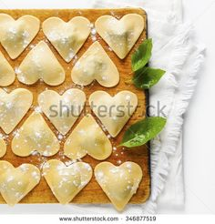 ravioli in a heart shape. cutting board with a group of raw freshly homemade ravioli . ready to be cooked. food romantic